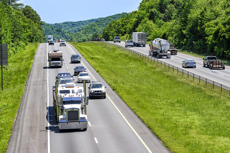 Trucks, cars and SUVs roll down an interstate highway in eastern Tennessee. A steady mix of trucks, cars and SUVs roll down an interstate highway in eastern royalty free stock images