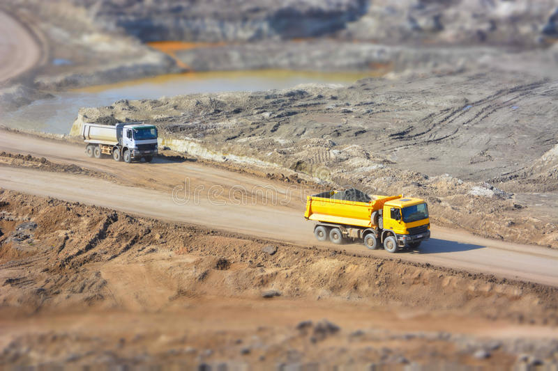 Trucks in a coal mine. A grey and yellow truck in a coal mine, transporting the dirt from the mine stock photo