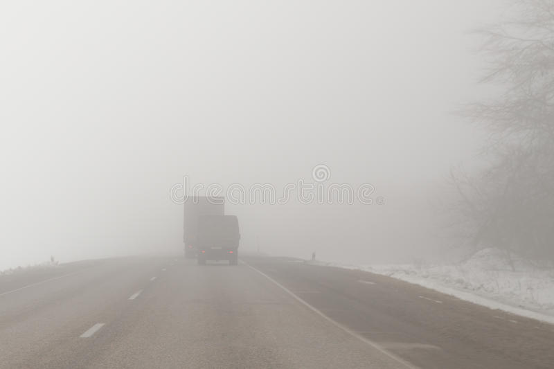 Trucks on a foggy road. Trucks driving on an extremely foggy road royalty free stock image