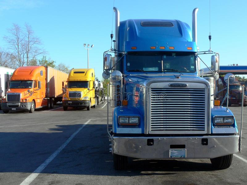 Trucks: front on. Three trucks parked in service station plaza royalty free stock photo