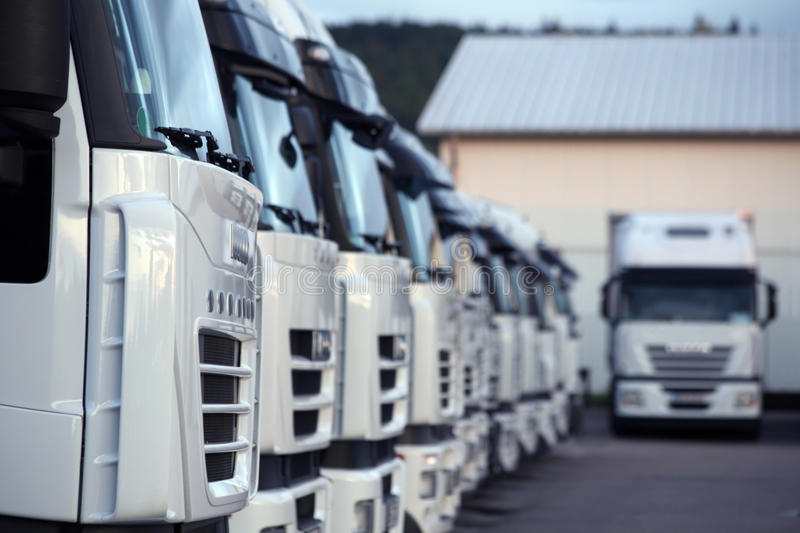 Trucks parked in depot. Closeup of white commercial trucks parked in depot royalty free stock image