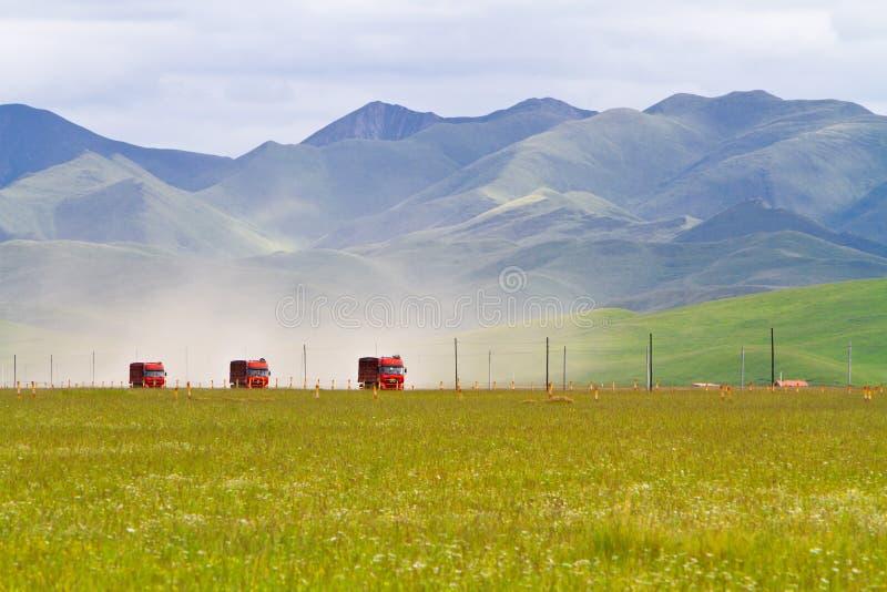 Trucks Passing Through Grassland Stock Photo