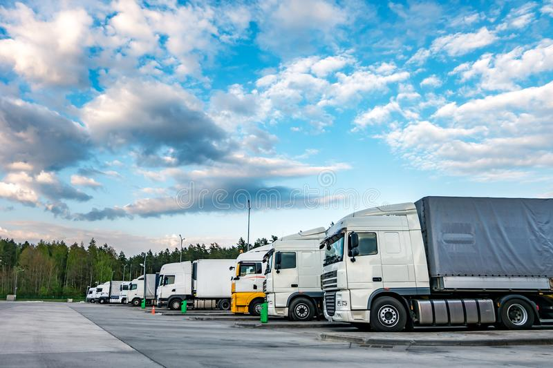 Trucks in a row with containers in the parking lot near forest , Logistic and Transport concept.  stock photography