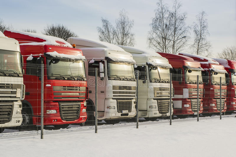 Trucks in a row. White and red color trucks parked in a row outdoors in winter time stock images