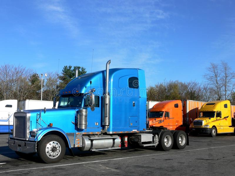 Trucks: side view. Three trucks parked in service station plaza stock image
