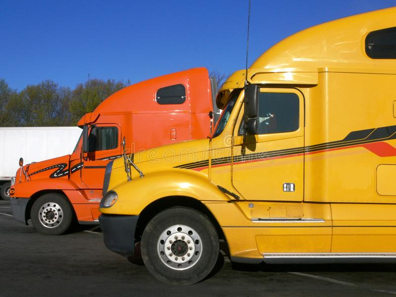 Trucks: side view of two. Two trucks parked in service station plaza royalty free stock photo