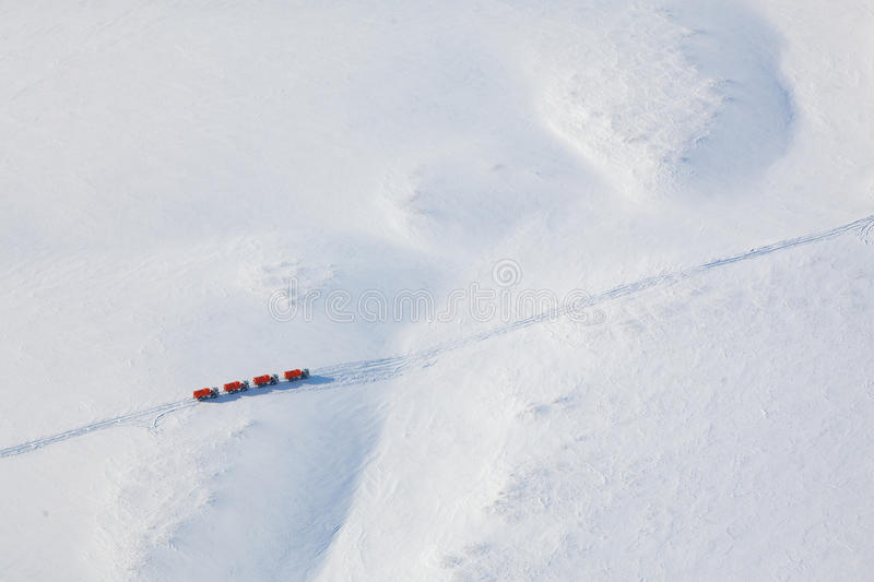 Trucks in winter tundra from above. Trucks moving through out road in the snow covered tundra in vicinity of oil field, top view royalty free stock image
