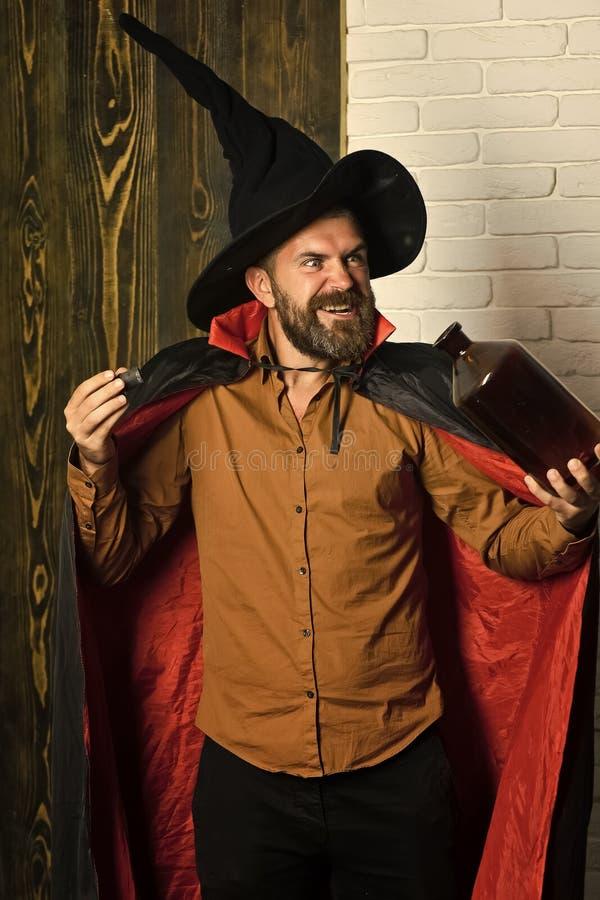 Truco de conjuración del mago del hombre de Halloween con la botella imágenes de archivo libres de regalías