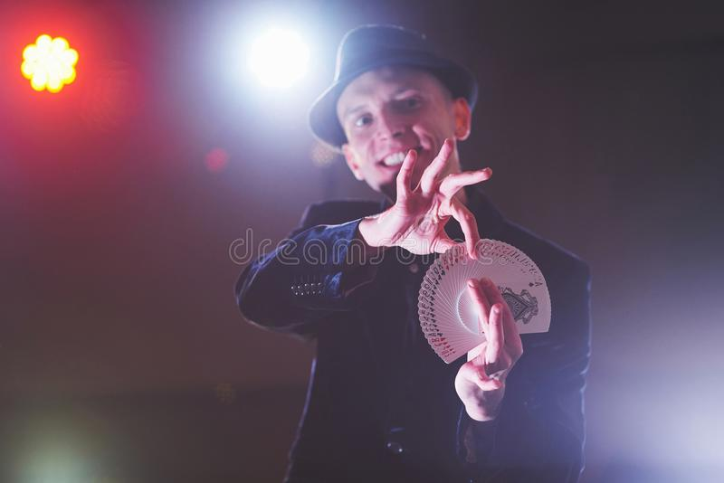 Truco de la demostración del mago con los naipes Magia o destreza, circo, jugando Prestidigitador en sitio oscuro con niebla imágenes de archivo libres de regalías