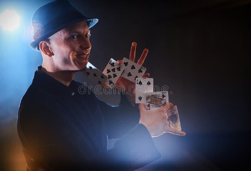 Truco de la demostración del mago con los naipes Magia o destreza, circo, jugando Prestidigitador en sitio oscuro con niebla imagen de archivo
