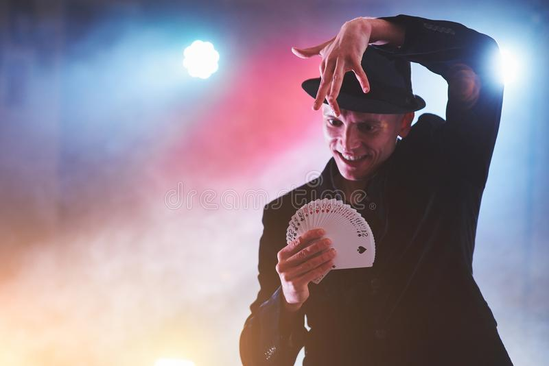 Truco de la demostración del mago con los naipes Magia o destreza, circo, jugando Prestidigitador en sitio oscuro con niebla fotografía de archivo libre de regalías