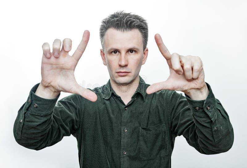 Truco m?gico Retrato de la foto de un hombre europeo joven que muestra ambas de su palma abierta Aislado en el fondo blanco imagen de archivo