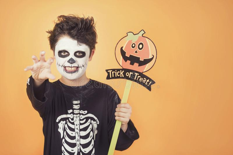 Truco o convite Niño divertido en un traje esquelético con la calabaza de Halloween foto de archivo libre de regalías
