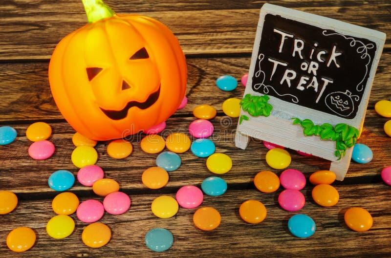 Truco o invitación, calabaza de la decoración de Halloween de la Jack-o-linterna con el caramelo en fondo de madera foto de archivo