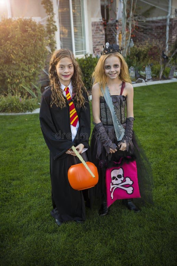 Truco que va de los niños o el tratar en Halloween en sus trajes imagen de archivo