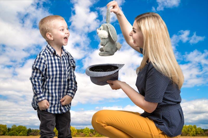 Trucs met een konijn Een jonge moeder toont weinig jongen magisch trucskonijn in de hoed Vriendschappelijke familie, vermaak stock foto