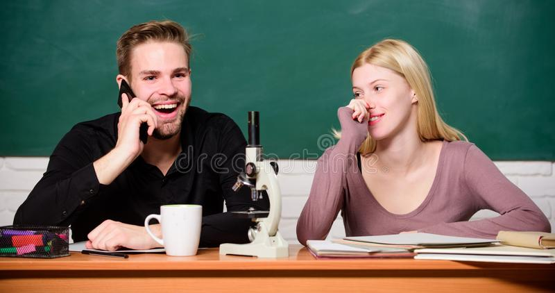 Trudny uniwersyteta temat eksperyment naukowy Facet i dziewczyna przy biurkiem z mikroskopem Studiowa? w szkole wy?szej lub obraz royalty free