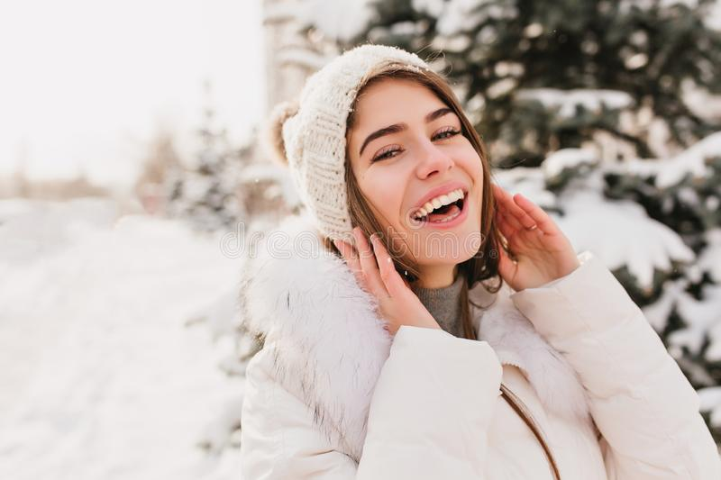 True brightful emotions of winter girl in knittted hat smiling to camera on street full with snow. Closeup portrait royalty free stock images