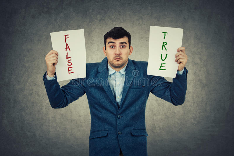 True or false. Confused young businessman holding two white papers try to choose between true or false, grey wall background. Human emotion, face expression royalty free stock images