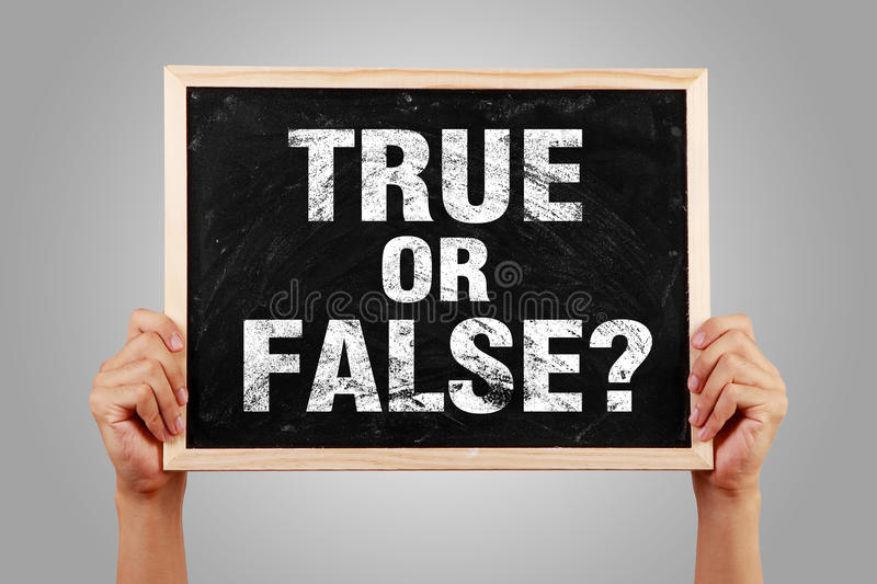 True Or False. Hands holding small blackboard with text True Or False against gray background stock photos