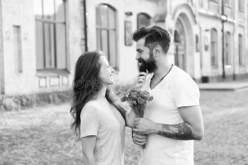 True feelings. Pick up girl for date. Bearded hipster fall in love. Couple meeting for date. Bouquet gift. Man giving stock photos