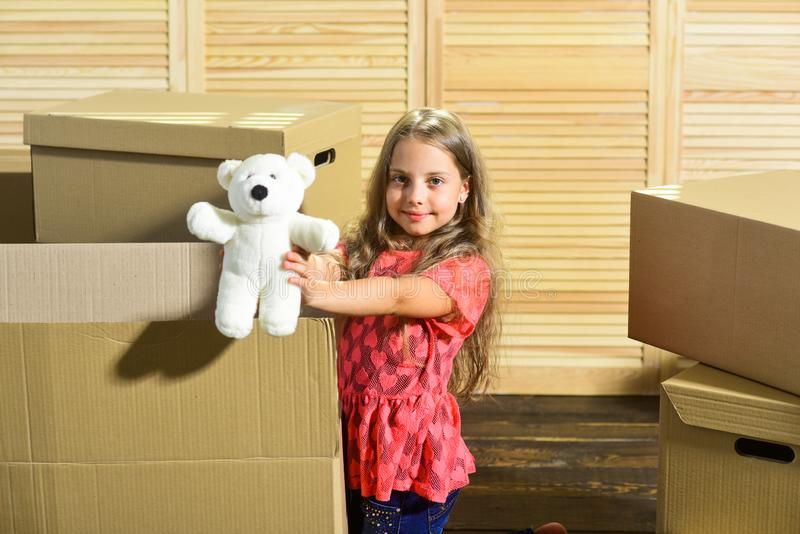 Only true friend. Girl child play with toy near boxes. Move out concept. Packaging things. Stressful situation. Divorce royalty free stock image