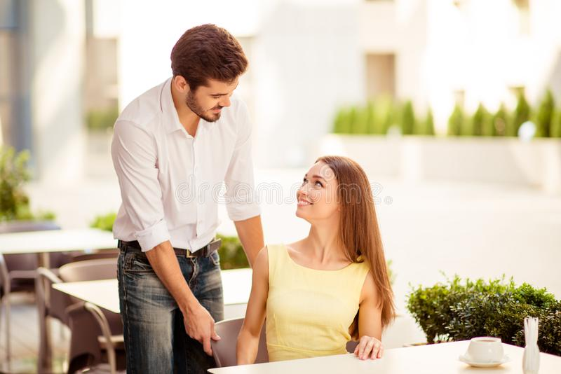 True gentleman! Young handsome brunet lover is adjusting the chair of his happy lady, both well dressed, at a sunny terrace of res royalty free stock image