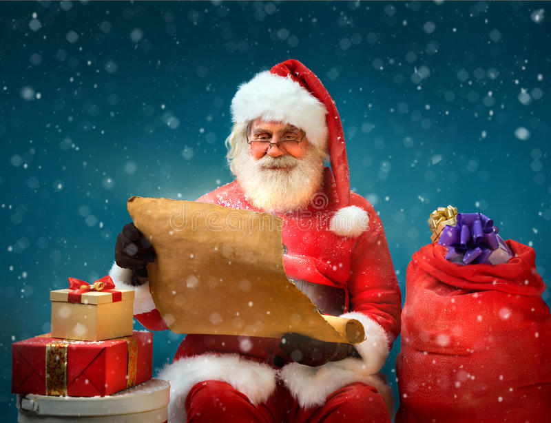 True Santa Claus reads long list of gifts for children on blue background. stock photo