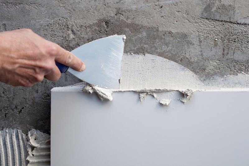 Truelle de spatule de construction dans le travail de tuile photographie stock