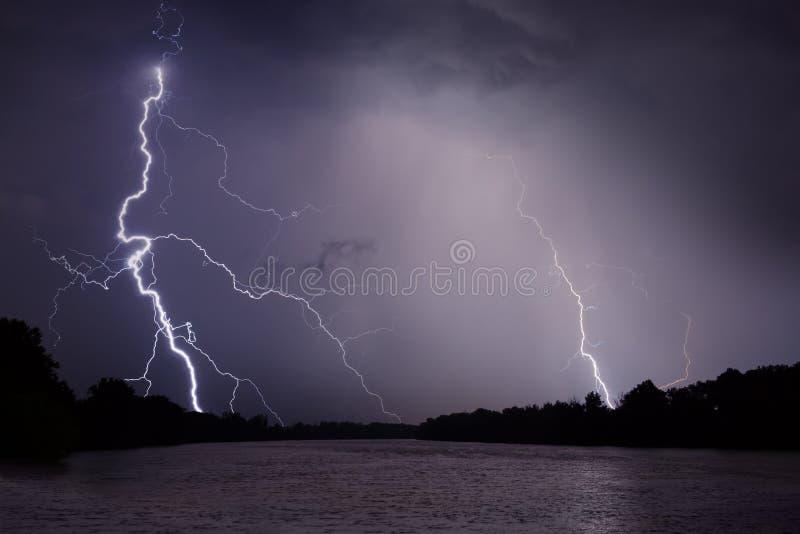 Trueno, relámpagos y lluvia durante tormenta sobre el río y el bosque fotografía de archivo libre de regalías
