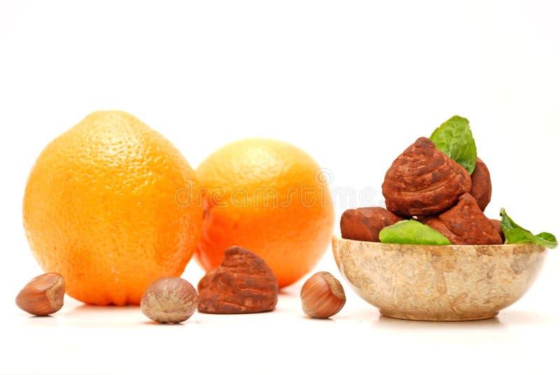 Trufas, avellanas y naranjas de chocolate foto de archivo