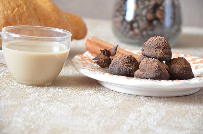 Trufas de chocolate con y canela Caramelo, chocolate, cruasán y una taza de café foto de archivo