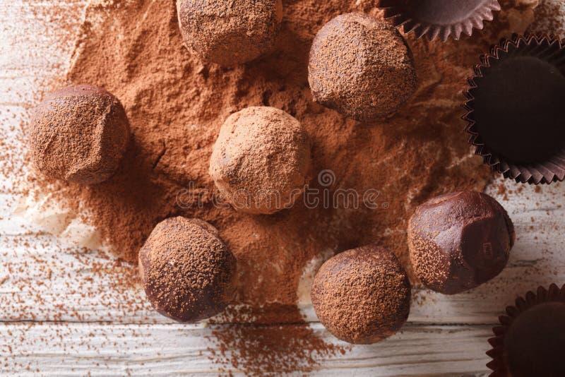 Trufas de chocolate en primer del cacao en una tabla top horizontal v fotografía de archivo