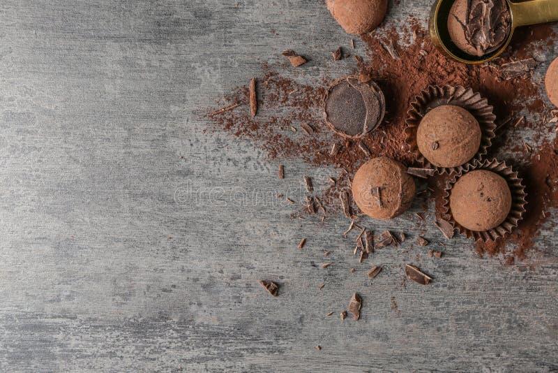 Trufas de chocolate saborosos com pó de cacau na tabela cinzenta imagem de stock
