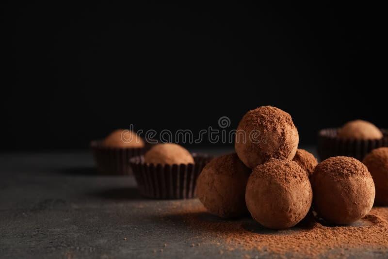 Trufas de chocolate saborosos pulverizadas com cacau na tabela foto de stock