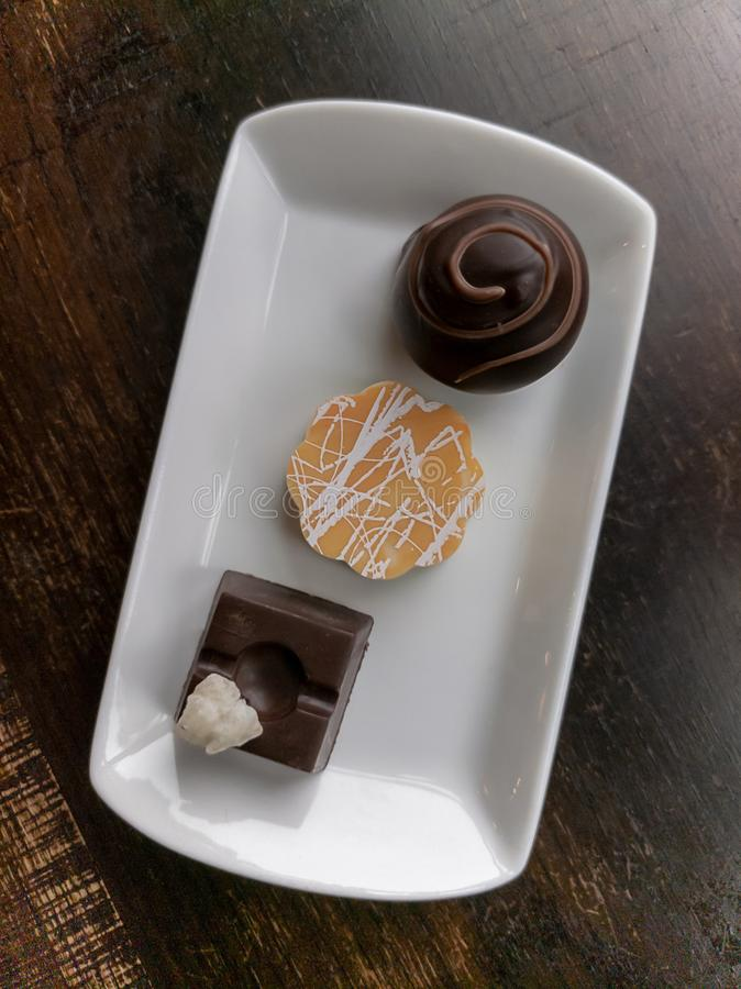 3 trufas de chocolate sortidos em um prato branco com tabela de madeira imagens de stock