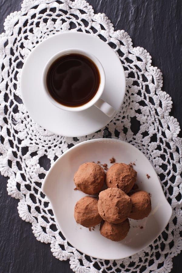Trufas de chocolate y primer del café en la tabla Vertical a fotos de archivo libres de regalías