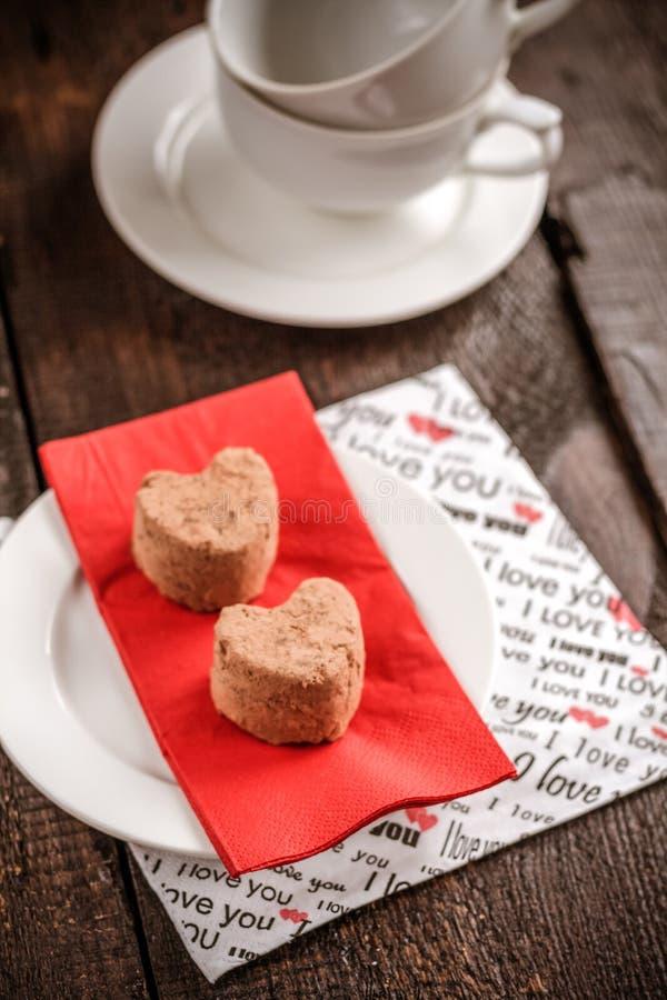 trufas em um coração em um guardanapo vermelho em uma tabela escura, contra um b imagens de stock royalty free