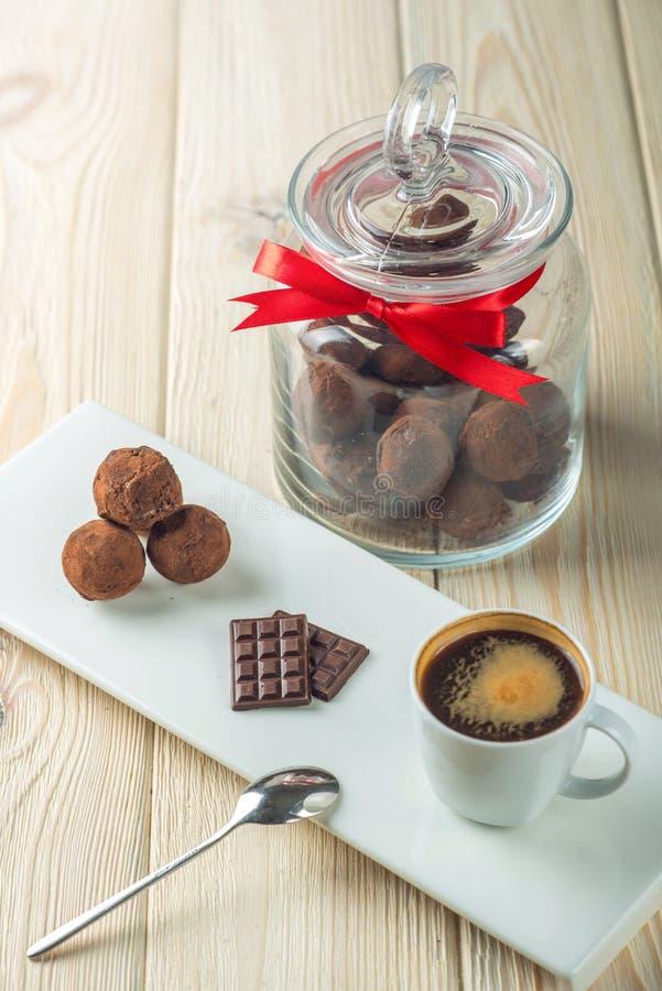 Truffes de boules de chocolat sur une soucoupe à côté d'un pot de sucrerie et d'une tasse de café Le concept des cadeaux délicieu images stock
