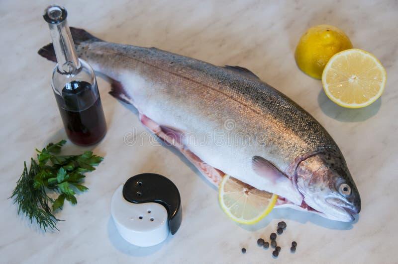 Truite crue avec la vigne rouge, tranches de citron, groupe de verts, poivre et sel sur un fond de marbre Plat de poisson frais photos libres de droits