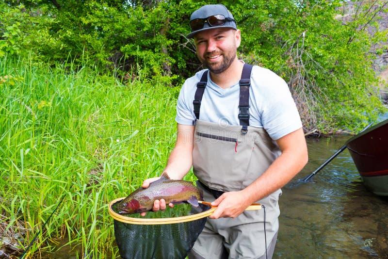 Truite de Holding Trophy Rainbow de pêcheur de mouche image stock
