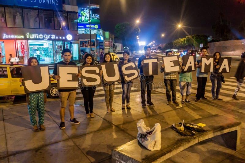 TRUJILLO, PERU - 6 DE JUNHO DE 2015: Grupo de ama local do te de Jesus do texto das mostras dos jovens Significa que Jesus ama o  imagem de stock