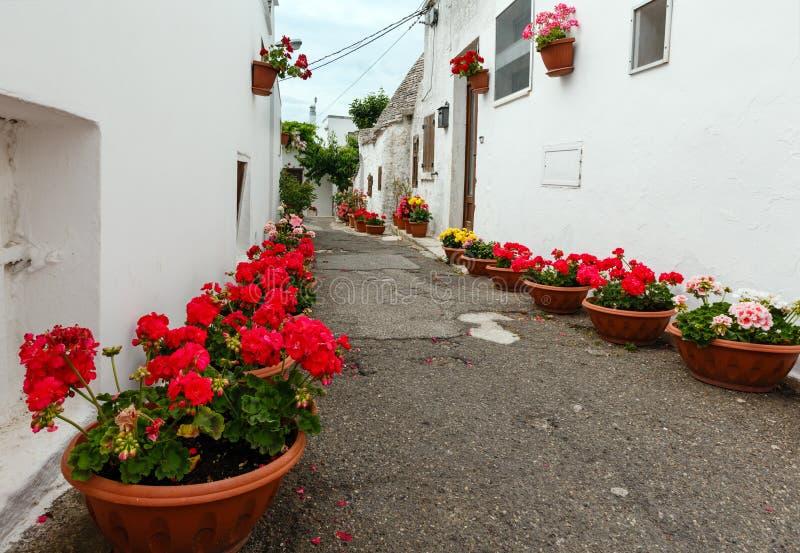 Trulli abriga a rua em Alberobello, Itália imagem de stock