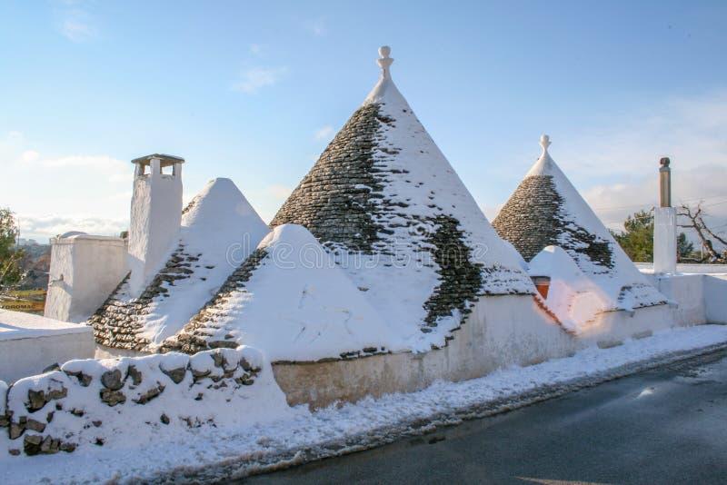 Trulli mit Schnee, traditionelle alte Häuser stockfotos