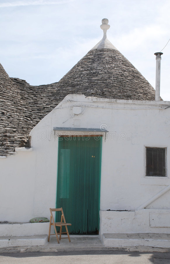 Trullo Door with Chair, Alberobello. The door of a trullo in Alberobello in Puglia, southern Italy. The trulli, which are protected under UNESCO World Heritage stock images