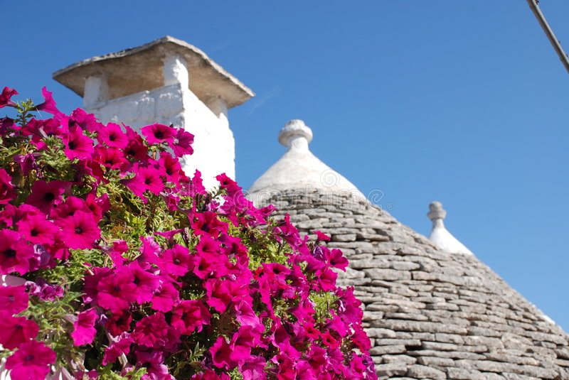 Trullo Roof with Pink Flowers 1. The roof of a trullo in Alberobello (Puglia, southern Italy), with pink flowers in the foreground. The trulli, which are stock image