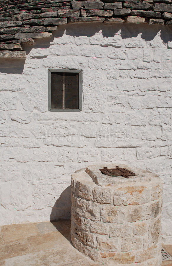 Trullo Window and Well. The window of a trullo in Alberobello in Puglia, southern Italy, with a well outside the house. The trulli, which are protected under stock photo
