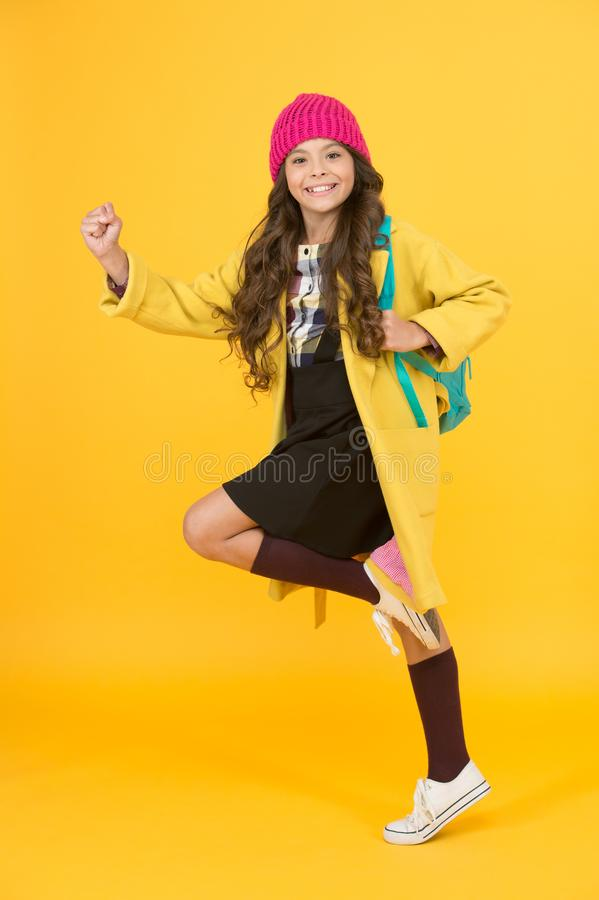 Truly energetic. Energetic girl hurry to school. Active small child on yellow background. High energy schoolkid. Little royalty free stock photography