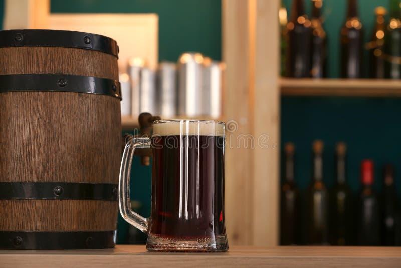 Trumma och exponeringsglas av öl på tabellen i stång arkivbild