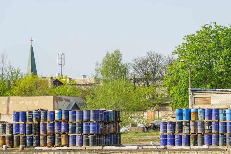 Trummor med kemiska produkter i portkajen, kyrka i bakgrunden arkivfoto